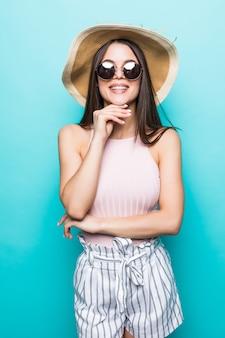 青い壁に隔離されたごちそう旅行やパーティーの準備ができて帽子とサングラスの夏の旅行の女性。休日を考えている魅力的な笑顔の女の子。夏の気分。