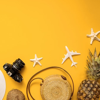 Summer traveler accessories flat lay. straw hat, retro film camera, bamboo bag, sunglasses, coconut, pineapple, starfish, air plane over yellow background