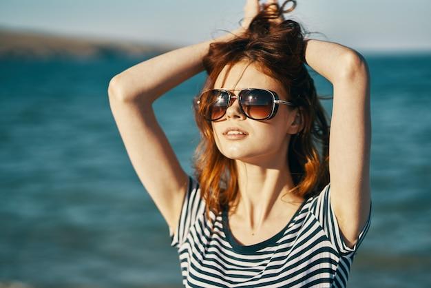 海の近くのビーチで夏の旅行者が彼女の手で頭に触れてトリミングされたビュー