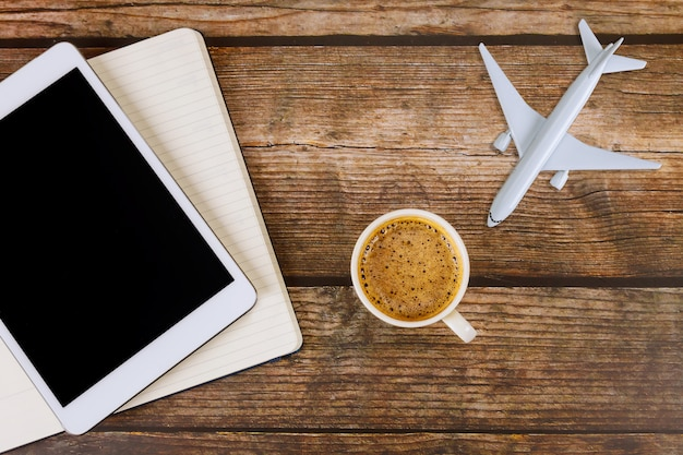 Summer for traveling concept on wooden table background travel concept with using digital tablet airplane model plane with blank paper notes, coffee cup