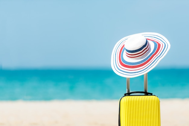 Summer traveling and planning with yellow suitcase luggage with big hat fashion in the sand beach. travel in the holiday, blue sky and beach background. summer and travel concept