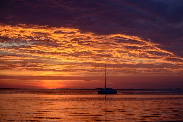 海の海水の日没のヨットで水に乗って夏の旅行ヨットボート