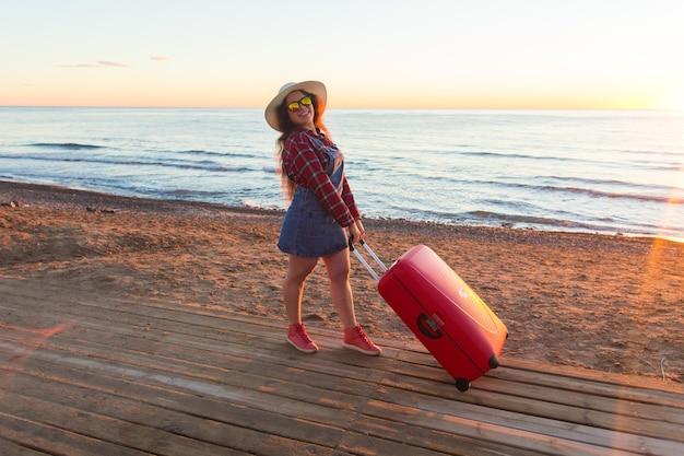 Концепция лета, путешествий и каникул - счастливая молодая женщина с чемоданом на берегу моря.