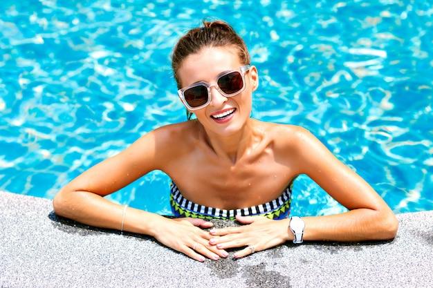夏のトレンディは、リラックスしてプールで泳いでいるセクシーな日焼けした女性のファッションポートレートを閉じます。明るいビキニとサングラスをかけ、笑顔で