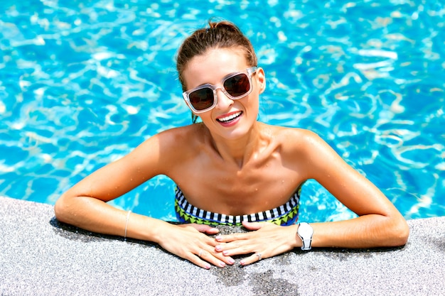 Summer trendy close up fashion portrait of sexy tanned woman relaxed and swimming at pool. wearing bright bikini and sunglasses, smiling and looking