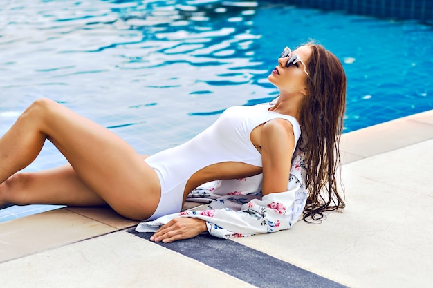 Summer trendy portrait of stunning sportive woman relaxed near pool at luxury hotel