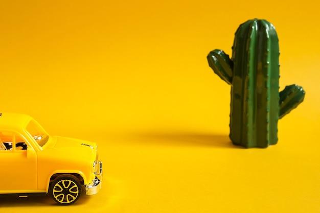 Летнее путешествие на машине - желтая машина на фоне кактуса - путешествие в пустыню, к морю. самостоятельные путешествия, внутренний туризм. такси на обзорную экскурсию. копировать пространство