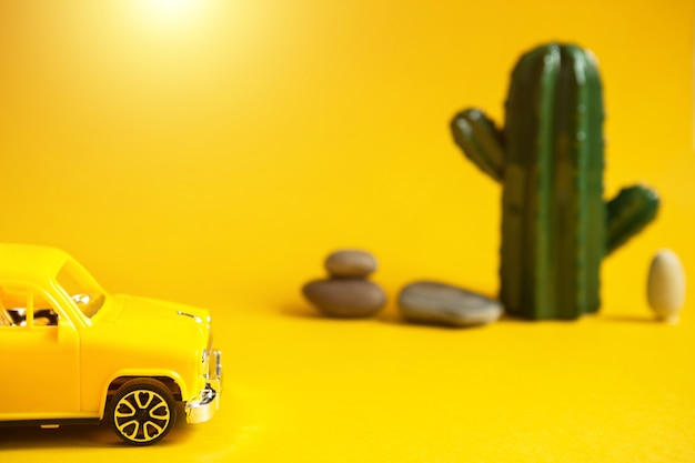 Summer trip by car-a yellow car on a background with a cactus-a tour to the desert, to the sea. independent travel, domestic tourism. taxi for a sightseeing tour. copy space