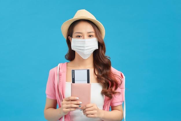 Covid-19での夏の旅行。旅行を夢見ているフェイスマスクを身に着けている女性