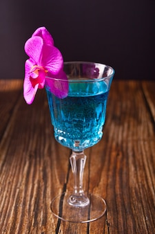 Летний тропический синий коктейль украшен фиолетовым цветком орхидеи на деревянном фоне.