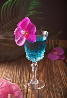 Summer tropical blue cocktail decorated purple orchid flower on the wooden background.