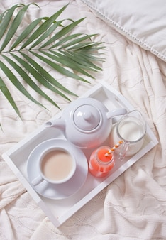 Summer tropical breakfast with cup of tea, teapot and refreshing exotic juice in a bottle with straw on a white tray under the palm leaf