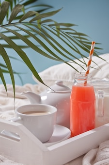 Summer tropical breakfast with cup of tea, teapot and refreshing exotic juice
