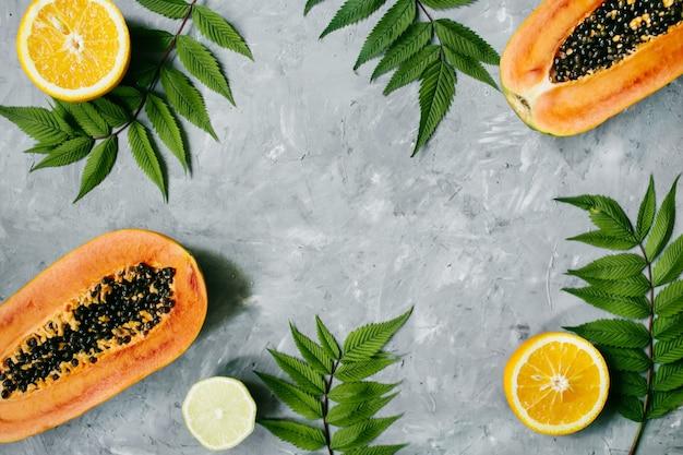 夏の熱帯の構成。灰色の背景に緑の葉とトロピカルフルーツ(パパイヤ、オレンジ、レモン)。夏のコンセプト。フラットレイ、上面図、コピースペース。高品質の写真
