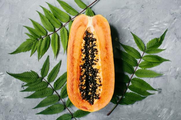 夏の熱帯の構成。健康食品のコンセプト。緑の葉と灰色の背景にパパイヤ。夏のコンセプト。フラットレイ、上面図。高品質の写真
