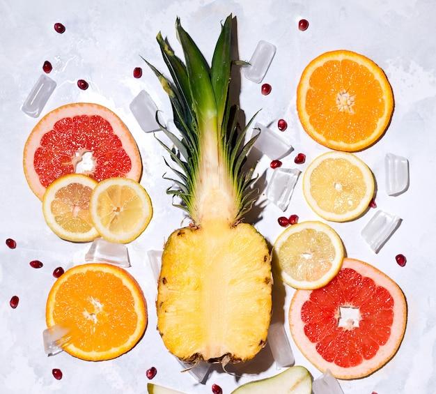Летние тропические фрукты ананас, грейпфрут, апельсин, лимон на бетонном пространстве.