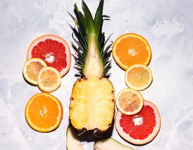 Летние тропические фрукты, нарезанные на сером пространстве