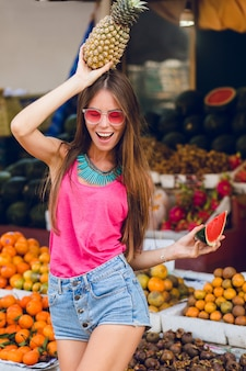 Summer tropical girl in pink sunglasses on market on fruits market. she holds ananas on head and slice of watermelon. she looks enjoyed