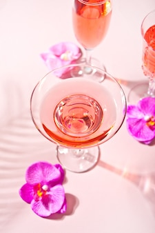 Summer tropical pink cocktail in a different glasses decorated pink orchid flowers. top view.