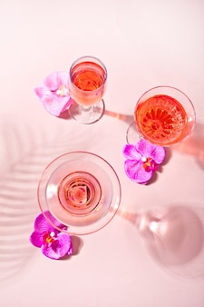 Summer tropical pink cocktail in a different glasses decorated pink orchid flowers.