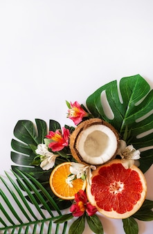 Летний тропический фон темы или шаблон с пространством для текста, различных фруктов, зеленых листьев и цветов. яркий летний фон