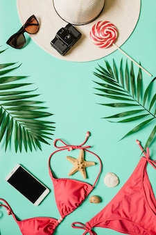 Summer tropical vacation flat lay concept with women accessories and swimwear on abstract colorful pastel background