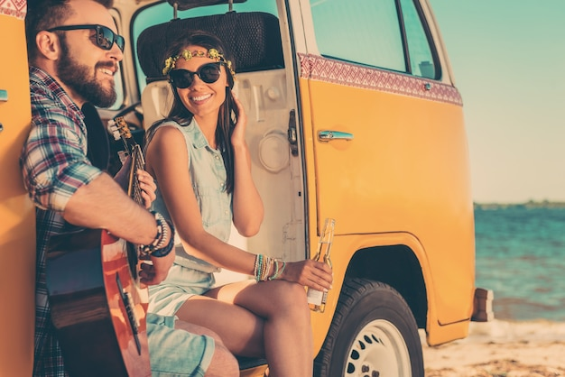 Летние мелодии. счастливая молодая пара наслаждается временем вместе, сидя в своем ретро-минивэне на фоне моря