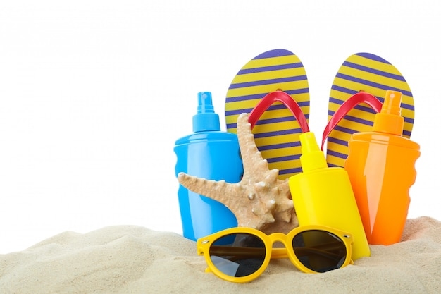 Summer vacation accessories in clear sea sand isolated on white background. summer vacation