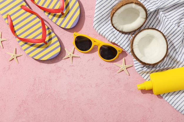 Summer vacation accessories on pink, space for text