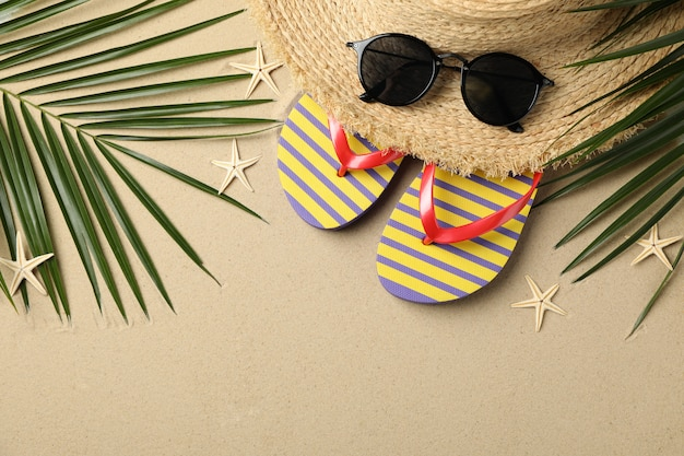 Summer vacation accessories on sea sand, space for text