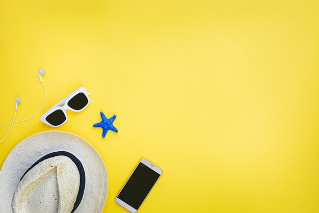 Summer vacation accessories. straw hat, white sunglasses, earphones and smartphone over yellow background. copy space, flat lay, mock-up.