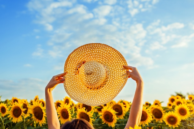 Summer vacation accessories. woman walking in blooming sunflower field raised hat up