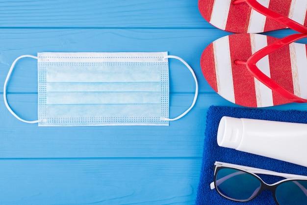 夏休みと健康保護の概念。上の俯瞰図のクローズアップ写真タオルサングラス日焼け止めマスクとコピースペースで青い木製の背景に分離されたフリップフロップ