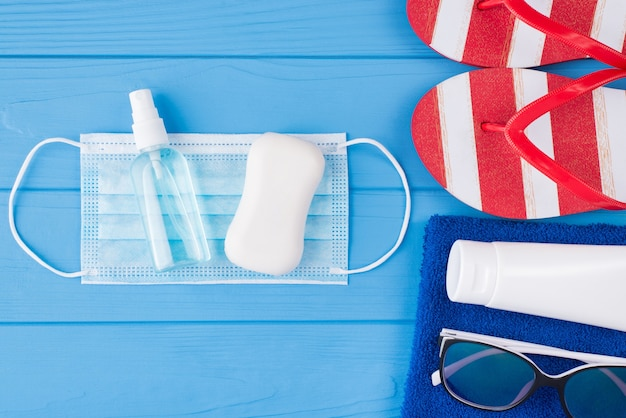 夏休みと健康保護の概念。上の俯瞰図のクローズアップ写真タオルサングラス日焼け止めマスク消毒石鹸とコピースペースで青い木製の背景に分離されたフリップフロップ