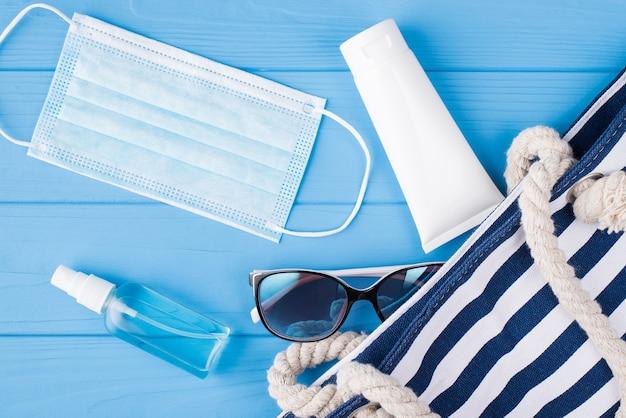 夏休みと検疫の概念。青い背景で隔離の手指消毒剤マスク日焼け止めサングラスとバッグの俯瞰写真の上の上