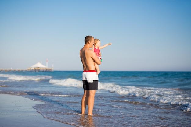 夏休みと旅行のコンセプト-ビーチで小さな娘と一緒に歩く幸せな父