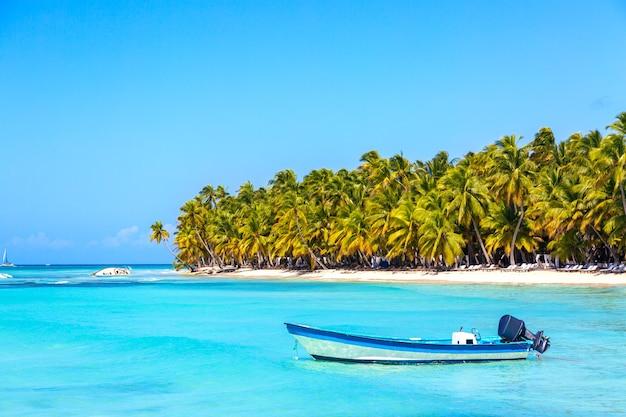 夏休みと熱帯のビーチのコンセプト。ヤシの木とターコイズブルーの海と砂浜の青いボート。休暇の島。