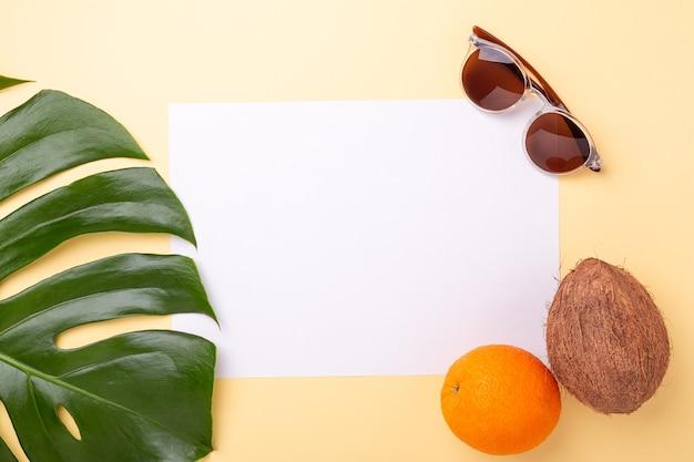 Фон летних каникул. чистый лист бумаги, лист монстеры и экзотические фрукты на желтом фоне - изображение