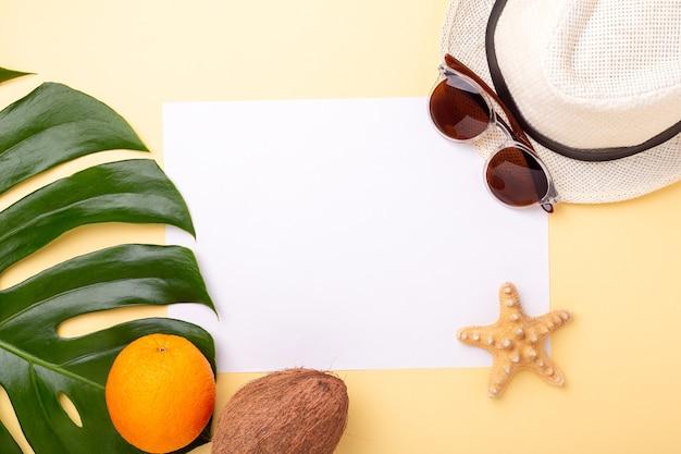 여름 휴가 배경. 빈 종이, 몬스 테라 잎과 노란색 배경에 이국적인 과일