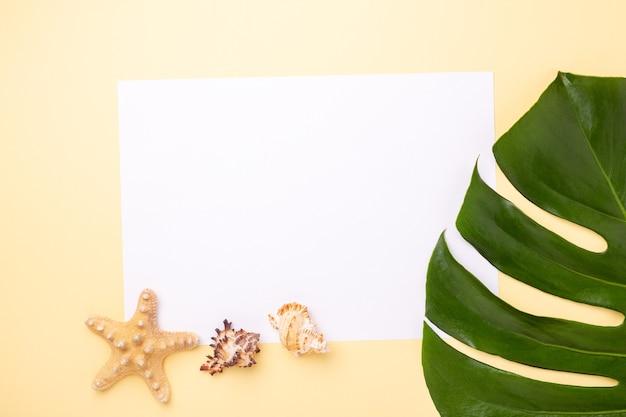 Фон летних каникул. чистый лист бумаги, лист монстеры, ракушки и морские звезды на желтом фоне - изображение
