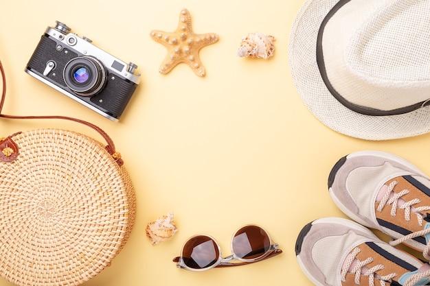 Фон летних каникул. кроссовки, сумка из ротанга, солнцезащитные очки, шляпа и ретро-камера