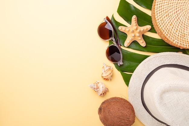 Баннер летних каникул. сумка из ротанга, солнцезащитные очки, шляпа и экзотические фрукты на желтом фоне.