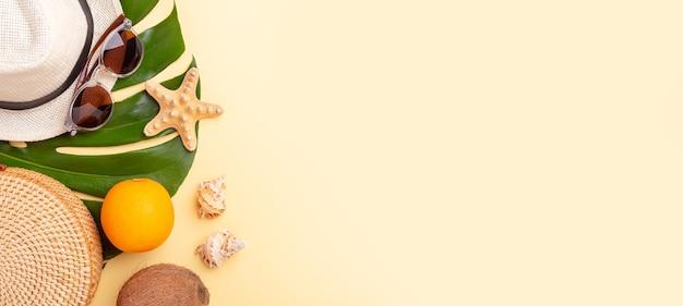 여름 휴가 배너. 등나무 가방, 선글라스, 모자 및 노란색 배경에 이국적인 과일.