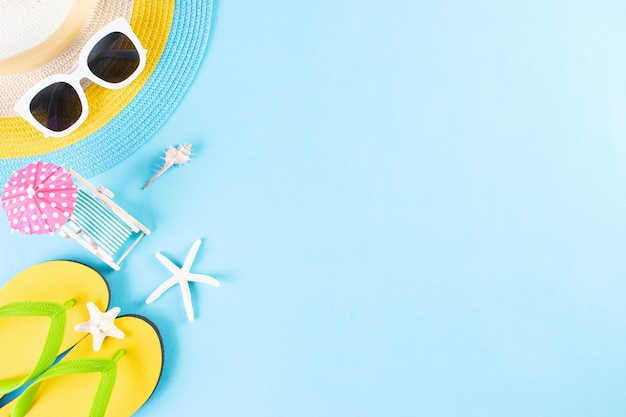 Summer or vacation. beach hat, sunglasses, sunbed, flip flops on light blue background. copy space.