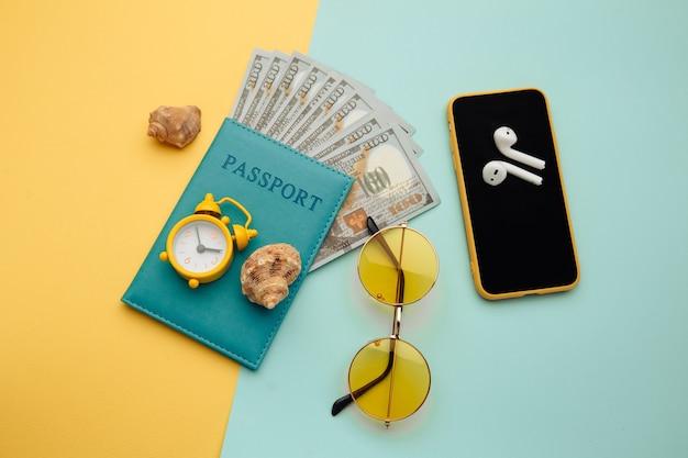 夏休みの構成。サングラス、スマートフォン、シェル、パスポートと紙幣