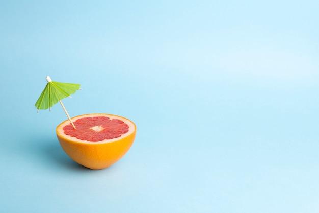 夏休みのコンセプトです。色付きの背景にカクテルの傘とグレープフルーツ。熱帯、太陽、ビーチ、ビタミン、果物、夏、そして良い気分