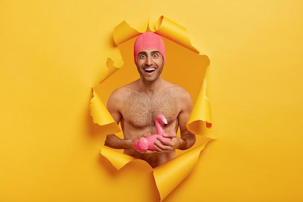 여름 휴가 개념. 좋은 몸매의 즐거운 남자, 벌거 벗은 몸통, 분홍색 수영 모자 착용, 부풀린 플라밍고 보유