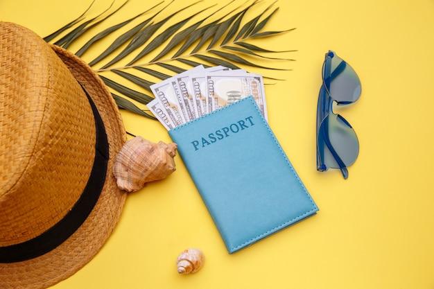 夏休みのコンセプト。黄色のテーブルにお金、サングラス、帽子のパスポート