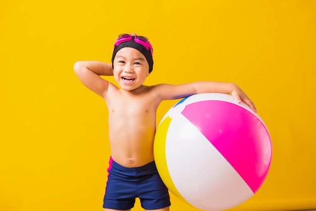 Summer vacation concept, portrait asian happy cute little child boy smiling in swimsuit hold beach ball, kid having fun with inflatable ball in summer vacation, studio shot isolated yellow