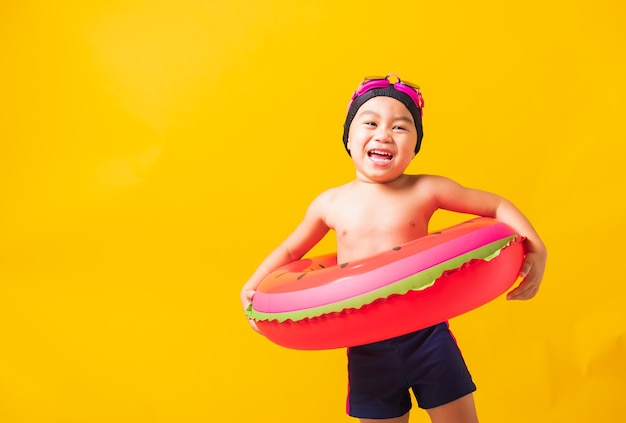 Summer vacation concept, portrait asian happy cute little child boy wear goggles and swimsuit hold watermelon inflatable ring, kid having fun on summer vacation, studio shot isolated yellow